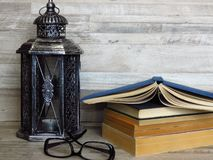 A very old silver lantern, a pile of old books, a pair of glasses on bleached oak background. Rustic, retro style. Handicrafts, craftsmanship, education royalty free stock images