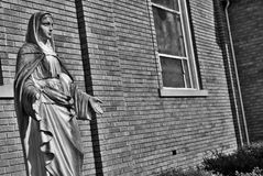 Very old statue bnw. Very old statue in front of a church black and white royalty free stock photo