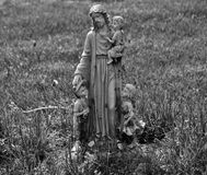 Very old statue in a cemetery. Very old statue / headstone in a cemetery stock photo