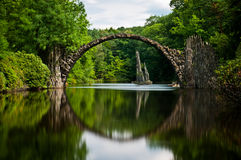 Very Old Stone Bridge Over The Quiet Lake With Its Reflection In The Water Stock Photos