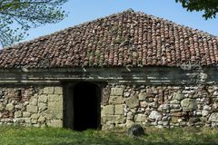 Very old stone building house with red roof and entrance in forest Stock Photo
