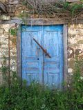 Blue Wooden Doors on Old Stone Greek Village House. A very old stone and mud owner built built Greek village house, with faded and flaking blue painted wooden Stock Photos