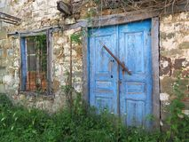 Blue Wooden Doors on Old Stone Greek Village House. A very old stone and mud owner built built Greek village house, with faded and flaking blue painted wooden Stock Photo