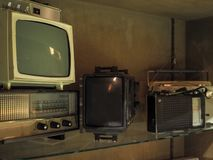 Old televisions and radios on a shelve royalty free stock photography
