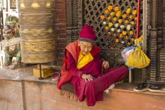 A very old Tibetan Buddhist monk in red and yellow clothes is sitting near a rotating prayer drum royalty free stock photo