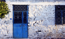Very old Turkish village house. Very old whitewashed Turkish village house with vivid blue wooden door Royalty Free Stock Images