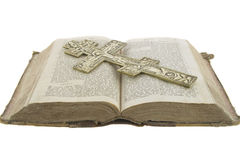 Very old vintage open bible and big church cross. On it isolated over white background Royalty Free Stock Images
