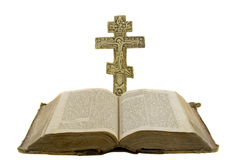 Very old vintage open bible and big church cross. Near to it isolated over white background Stock Photo