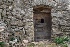 Very old weathered brown door made of wood. Stone house Island Cres, Croatia stock photo