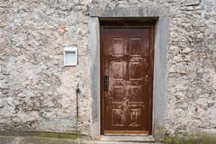 Very old weathered brown door made of wood. Stone house Island Cres, Croatia stock photography