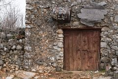 Very old weathered brown door made of wood. Stone house Island Cres, Croatia royalty free stock image