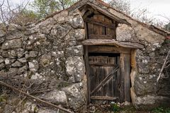 Very old weathered brown door made of wood. Stone shed Island Cres, Croatia royalty free stock photography