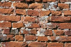Archtecture texture - Ancient red brick wall. Very old weathered, damaged, badly repaired hand made red brick wall close up Royalty Free Stock Images