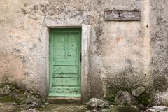 Very old weathered green door made of wood. House entrance in Beli Island Cres, Croatia royalty free stock photo
