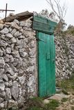 Very old weathered green door made of wood. Stone wall Island Cres, Croatia stock images