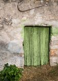 Very old weathered small fresh painted green door made of wood. Island Cres, Croatia stock photos