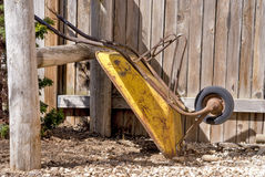 Wheel barrel leaning agains an old fence Stock Photography