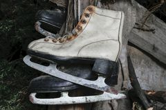 Very Old White and Black Rusty and Dirty Ice Skates Hanging in Warehouse royalty free stock photography