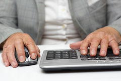 Very old woman typing on keyboard and using mouse Stock Photo