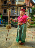 Very old woman with a walking stick in Bandipur. BANDIPUR, NEPAL - OCTOBER 22, 2015 : Very old woman walks with a walking stick in the street of Bandipur Stock Photo