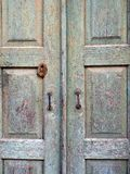 Very Old Wooden Doors. Very old panelled wooden doors, with textured faded and flaking blue-green paint, and tarnished metal door handles. The actual location is Royalty Free Stock Image