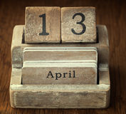 A very old wooden vintage calendar showing the date 13th April o. N wood background Royalty Free Stock Images