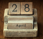 A very old wooden vintage calendar showing the date 28th April. On wood background Royalty Free Stock Images