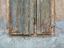 Very Old Wooden Window Shutters. Very old panelled wooden window shutters, with textured faded and flaking blue-green paint, and tarnished metal hinges. The Royalty Free Stock Images
