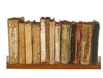 Very old and worn books on a wooden shelf isolated on white back Royalty Free Stock Photo