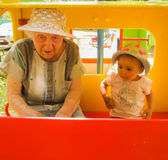 Very older grandmother talking with her little granddaughter on playground, both wearing bonnets, red blank board Royalty Free Stock Photography