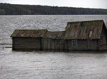 Very original houseboat village on lake. Abandoned wooden house. Very original houseboat village on lake, lake-habitation. Dying Russian village, traditional Stock Photography