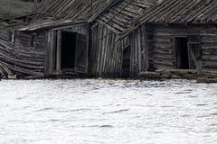 Very original houseboat village on lake. Abandoned wooden house. Very original houseboat village on lake, lake-habitation. Dying Russian village Royalty Free Stock Images
