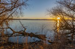 Sunset Over Barr Lake. Very peaceful scene of a calm Barr Lake, Barr Lake State Park, in Brighton, Colorado. The image was taken from the shore, and framed with royalty free stock image