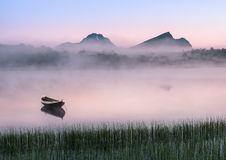 Very peaceful summer night with wooden boat and fog Stock Image