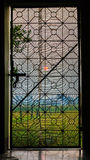 A very pleasant evening view from backdoor of house. You can see the rice field and sunset from the backdoor of my house plus the patterns of the door. A layer royalty free stock photo