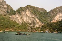 Fishers houses on green water in Halong Bay Stock Photos