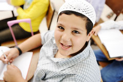 Very positive kid with white small hat sitting Royalty Free Stock Image