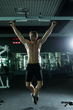Very power athletic guy , execute exercise tightening on horizontal bar, in sport-hall. Glamour light, look stare on camera Stock Images