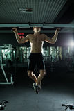 Very power athletic guy , execute exercise tightening on horizontal bar, in sport-hall. Glamour light, look stare on camera Stock Photos