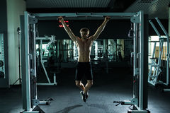 Very power athletic guy , execute exercise tightening on horizontal bar, in sport-hall. Glamour light, look stare on camera Royalty Free Stock Image