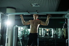Very power athletic guy , execute exercise tightening on horizontal bar, in sport-hall. Glamour light, look stare on camera Royalty Free Stock Images