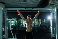 Very power athletic guy , execute exercise tightening on horizontal bar, in sport-hall. Glamour light, look stare on camera Stock Photo