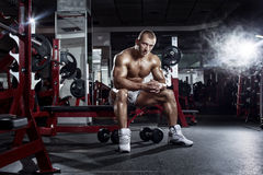 Very power athletic guy, relaxing after workout in gym Royalty Free Stock Photography