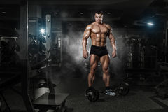 Very power athletic guy standing with barbell workout in the gym Stock Images
