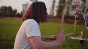 Very powerful and expressive drumming in the open field at sunset. Wonderful performance. Rock band stock footage