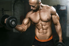 Very powerfull athletic guy working in gym with dumbbells stock images