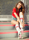 Very pretty brunette girl in a red top and jeans shorts and vintage roller derby has a rest sitting on the stairs. Outdoor. Metal Royalty Free Stock Photos