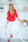 Very pretty sexy girl smiling in a red shirt next to the white b Stock Image