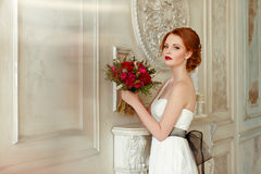 Very pretty sophisticated red-haired girl with a bouquet in hand. In the interiors of the studio Royalty Free Stock Images