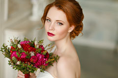Very pretty sophisticated red-haired girl with a bouquet in hand. In the interiors of the studio, close-up Royalty Free Stock Photos